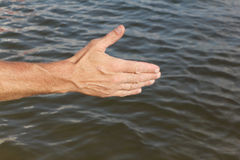 Suntanned male hand against of the water. Suntanned male hand against a surface of the water Stock Photography