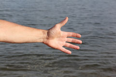 Suntanned male hand against of the water. Suntanned male hand against a surface of the water Royalty Free Stock Photo