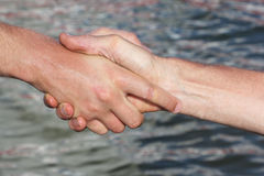 Suntanned male hands make handshake against a water. Surface Stock Photo