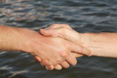 Suntanned male hands make handshake against a water surface. Suntanned male hands make handshake against a water Stock Photo