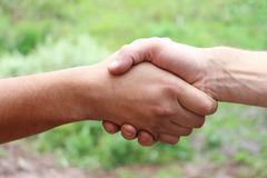 Suntanned male hands make handshake. Outdoor Royalty Free Stock Images