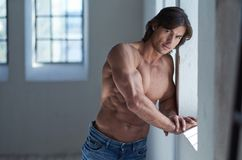 Portrait of suntanned muscular guy in denim jeans. Suntanned muscular male in blue jeans posing in natural light from window Stock Images