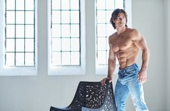 Suntanned muscular male in blue jeans posing. Suntanned muscular male in blue jeans posing in natural light from window Royalty Free Stock Images