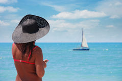 Suntanned woman on a beach. Woman on the beach looking at the fleeing sailboat Royalty Free Stock Photography
