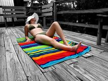 Suntanning girl. Girl sunbathing on a terrace Royalty Free Stock Image