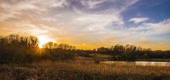 Suntset au-dessus de lac Pebsham en parc de campagne de vallée de Combe, près de Bexhill, le Sussex est, Angleterre photographie stock