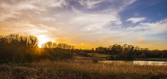 Suntset over Pebsham Lake in Combe Valley Countryside Park, near Bexhill, East Sussex, England stock photography