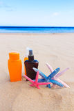 Suntun creams on sandy beach Stock Photography