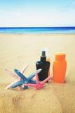 Suntun creams on sandy beach Royalty Free Stock Photography
