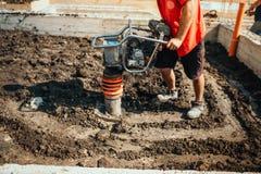 suolo comprimente del lavoratore dell'industria nel fondamento della casa facendo uso del compattatore fotografia stock