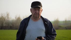Suolo dell'agricoltore maturo e smartphone d'esame usando che controlla rapporto di agricoltura in un campo stock footage