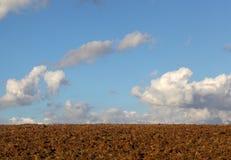 Suolo dell'aratro con un cielo blu e le nuvole Immagini Stock