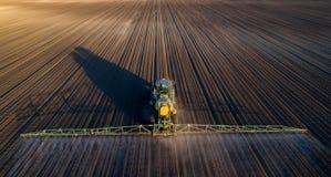 Suolo di spruzzatura del trattore nel campo Fotografie Stock Libere da Diritti