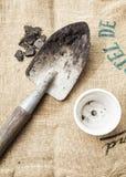 Suolo e pianta da vaso degli strumenti di giardinaggio sul fondo del sacco Fotografie Stock