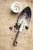 Suolo e pianta da vaso degli strumenti di giardinaggio sul fondo del sacco Fotografia Stock