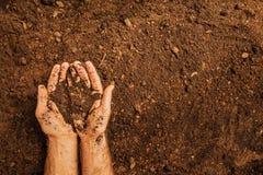 Suolo in mani del ` s dell'uomo del ` s dell'agricoltore sul fondo del campo Fotografia Stock Libera da Diritti