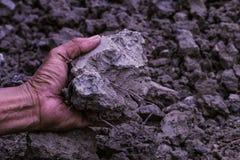 Suolo in mani dell'uomo dell'agricoltore del fondo nero del suolo concetto circa Fotografie Stock