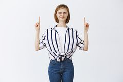Suona sospettoso Ritratto della femmina moderna astuta incerta con capelli biondi in blusa a strisce, smirking dal dubbio e immagine stock libera da diritti