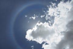Suoni l'alone in cielo blu, il sole è coperto da una nuvola bianca Immagine Stock