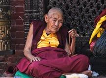Suora anziana vicino a Boudhanath Stupa fotografie stock libere da diritti