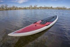 SUP paddleboard on lake shore Stock Photo