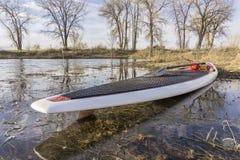 SUP paddleboard on lake shore Stock Image