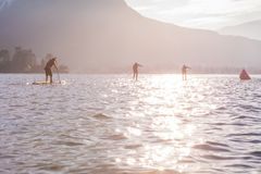 SUP racers are participating in sport event. Lake in France. Sunny winter day. excitement and rivalry stock images