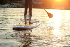SUP silhouette of young girl paddle boarding at sunset. SUP confident woman swimsuit standing with a paddle on the surfboard, legs stock photo