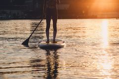 SUP silhouette of young girl paddle boarding at sunset. SUP confident women swimsuit standing with a paddle on the surfboard, legs royalty free stock photography