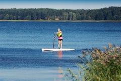 SUP sprawność fizyczna - kobieta na paddle desce w jeziorze Zdjęcie Stock