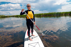 SUP stand up girl with a paddle 03. SUP stand up beautiful girl with a paddle on the board royalty free stock image