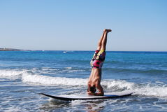 Man in headstand on SUP. Man performing headstand while riding waves on stand up paddle board or SUP on sunny day Stock Photo
