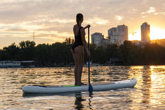 SUP Stand up paddle board woman paddle boarding19. SUP confident woman swimsuit standing with a paddle on the surfboard Royalty Free Stock Images