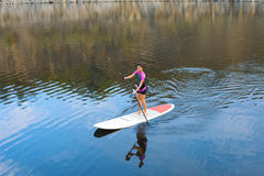 SUP Stand up paddle board woman paddleboarding. Confident woman standing with a paddle on the surfboard, yoga, fitness Stock Photos