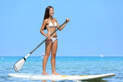 SUP Stand up paddle board woman paddleboarding. On Hawaii standing happy on paddleboard on blue water. Young biracial Asian Caucasian female model on Hawaiian Royalty Free Stock Photo