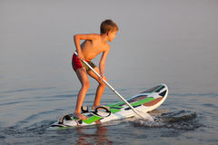 SUP (stand up paddle) learning. Little boy standing on the windsurfing board with paddle. Evening light Stock Photos