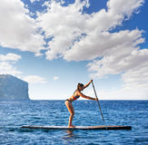 SUP Stand up Surf girl with paddle Royalty Free Stock Photo