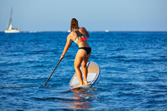 SUP Stand up Surf girl with paddle Stock Images