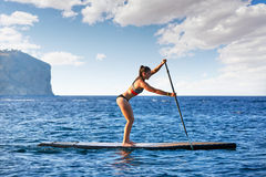 SUP Stand up Surf girl with paddle. In a blue ocean sea Royalty Free Stock Photography