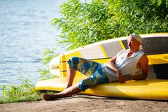 Sup surfer is relaxing in a river camping. Using sup like sofa is enjoying life and thinks about something Royalty Free Stock Photo