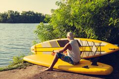 Sup surfer is relaxing in a river camping. Using sup like sofa is enjoying life and thinks about something Stock Photo