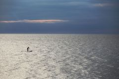SUP surfer at sea. Silhouette of woman - SUP surfer alone at sea in the twilight Royalty Free Stock Image