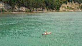 Sup surfer woman rowing on surfboard. Beautiful seascape. Man lying on board stock video footage