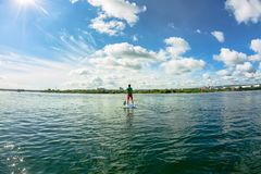 Sup surfing man stand up paddle boarder paddling at sunset on river.  Royalty Free Stock Images