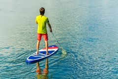 Sup surfing man stand up paddle boarder paddling at sunset on river.  Royalty Free Stock Photos