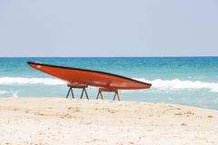 SUP tegen het blauwe overzees en het witte zand stock foto's
