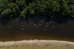 SUP unidentifiable people paddle boarding on a calm river during summer stock photography