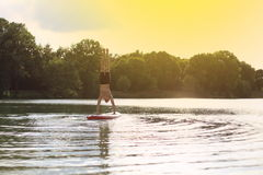SUP yoga stand up paddling handstand Stock Image