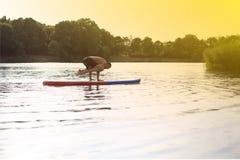 SUP Yogatribune die omhoog raad paddelen Stock Afbeelding