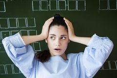 Supdrised girl in glasses sits against blackboard in classroom Stock Images